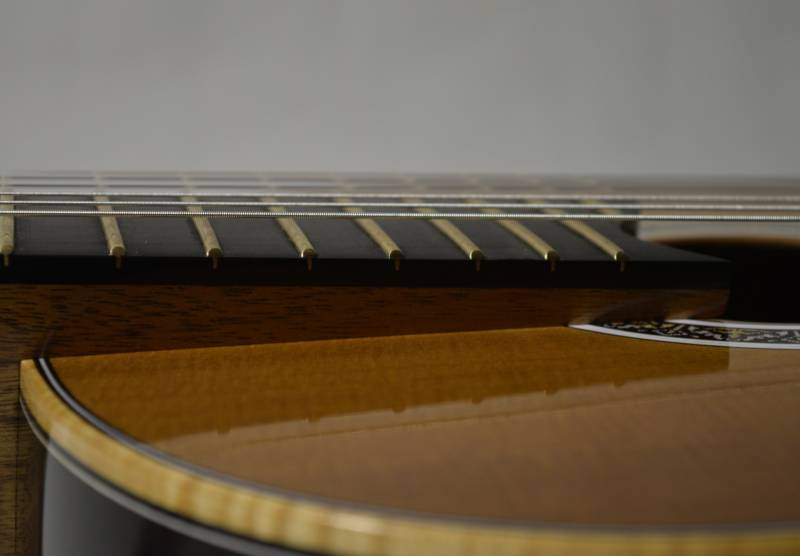 The top is sloped down and the neck angle slightly increased to increase response and facilitate playing above the 12th fret
